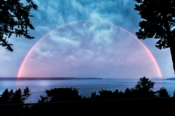 Pink rainbow over the water